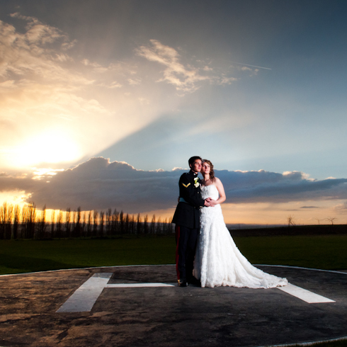 off camera flash shot of soldier groom and his bride on a helipad